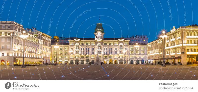 Das Rathaus, Palazzo del Municipio, ist das dominierende Gebäude auf dem Hauptplatz von Triest, der Piazza dell Unita d Italia. Triest, Italien, Europa. Beleuchteter Stadtplatz in der Abenddämmerung aufgenommen.