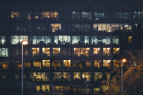 Beleuchtete Fenster eines Bürogebäudes bei Nacht Gebäude Lichter beleuchtet Reihen frontal breit Straßenlaternen Farbe Außenseite im Freien Großstadt urban