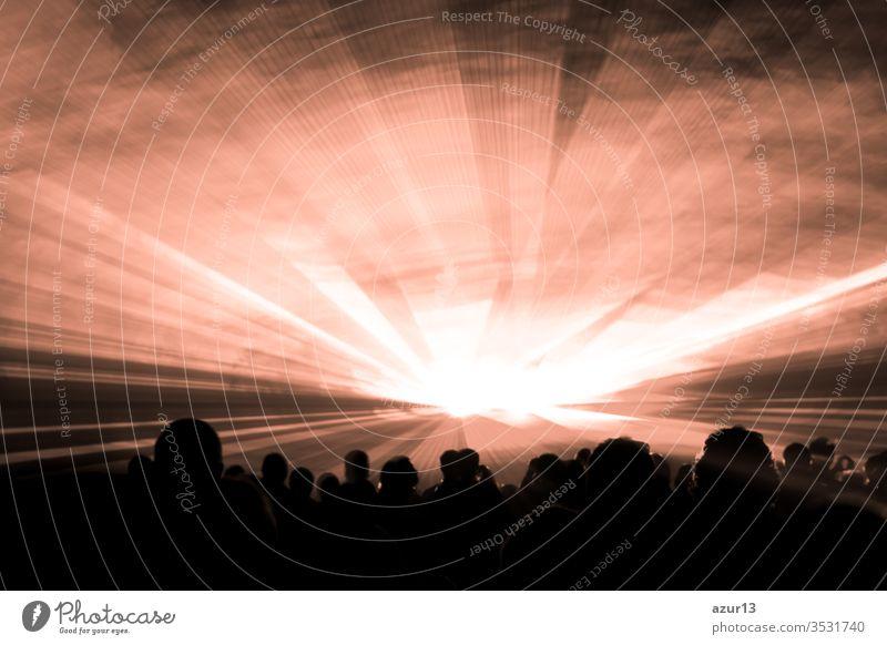 Bühne eines Nightlife-Clubs mit bronzener Lasershow, auf der sich Party-People drängen. Luxusunterhaltung mit Publikums-Silhouetten bei Nachtclub-Veranstaltungen, Festivals oder Silvester. Strahlen und Strahlen, die bunte Lichter ausstrahlen