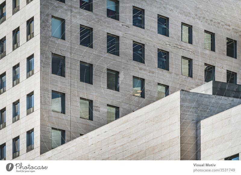 Geometrische Ansicht eines modernen Geschäftsgebäudes aus römischem Travertinmarmor Fassade Gebäude geometrisch Fenster Reihen Glas Perspektive Farbe im Freien