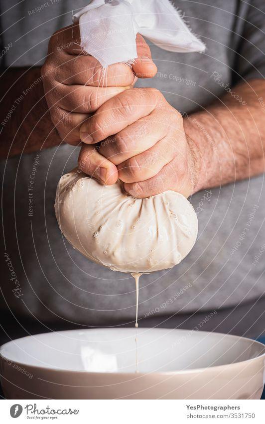 Horchata-Herstellungsverfahren. Mann beim Auspressen von Mandelmilch. Von Hand hergestellte Nussmilch Mandeln Milch Getränk Cocktail Erfrischungsgetränk Dessert