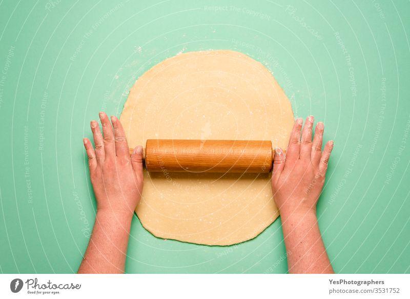 Einen Kuchen von oben betrachten. Frau, die den Teig auf dem grünen Tisch ausbreitet obere Ansicht Bäcker Bäckerei backen Koch Kruste Küche kulinarisch Dessert