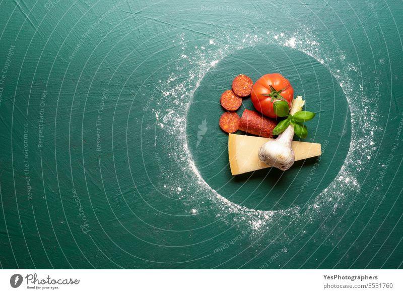 Pizza-Peperoni-Zutaten auf grünem Tisch, Draufsicht. obere Ansicht backen Basilikum Käse kreisen Fertiggerichte Essen zubereiten Abendessen flache Verlegung