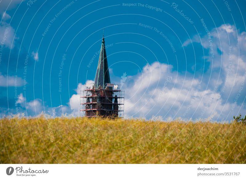 """"""" Mein Ziel """" Kornfeld mit Kirchturm.  Hinter einem Feld. Der Kirchturm hat ein Gerüst im unteren Bereich. Blauer Himmel und Wolken. Sonne Landschaft"""