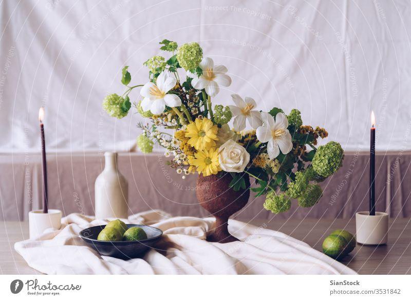 Stilleben mit einem schönen Blumen-, Kerzen- und Lindenstrauss Tisch Vase Hochzeit Blumenstrauß Dekoration & Verzierung weiß Hintergrund Innenbereich Kalk