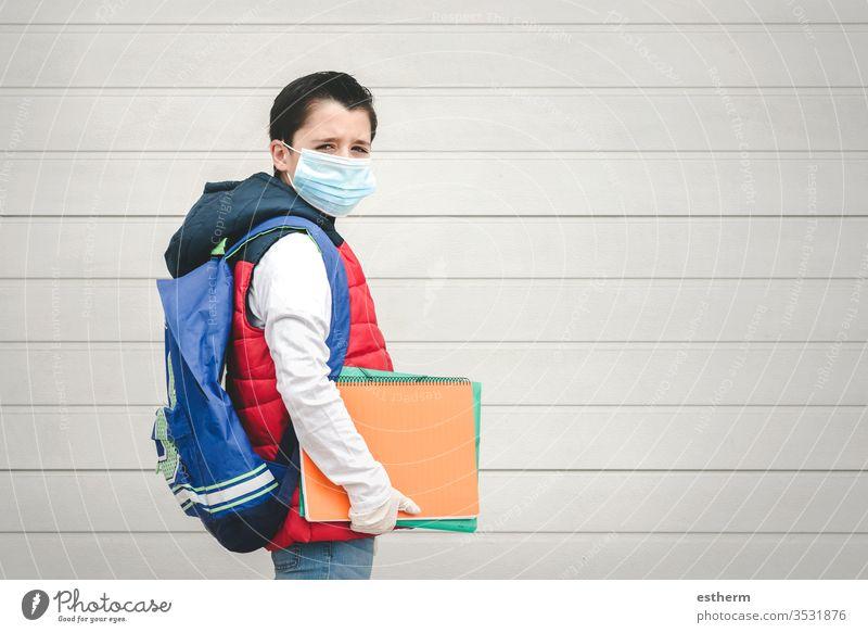 covid-19,Porträt eines Kindes mit medizinischer Maske und Rucksack auf dem Schulweg Coronavirus Virus Seuche Schule Schüler Pandemie Quarantäne