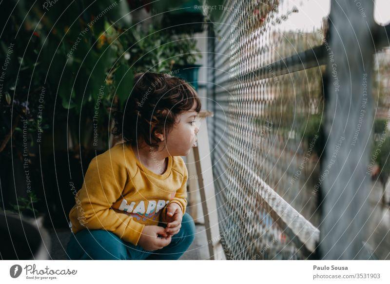 Kind auf dem Balkon Kindheit zu Hause Lifestyle Herbst authentisch fallen Balkongeländer Balkon-Bepflanzung grün Sperrung zu Hause bleiben Außenaufnahme Pflanze