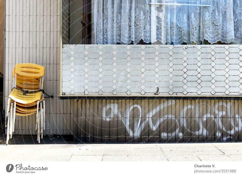 corona thoughts |Gelbe Stühle warten angekettet an einer Fünfziger-Jahre-Retro-Wand auf ihren Einsatz. Die coronavirus coronakrise Coronavirus SARS-CoV-2