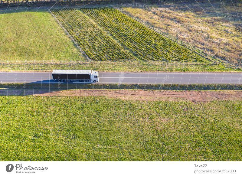 ein Lastwagen von oben in einer Frühlingswiesenlandschaft Straße Straße von oben Straße mit einem Auto Autofahren Auto von oben landwirtschaftlich