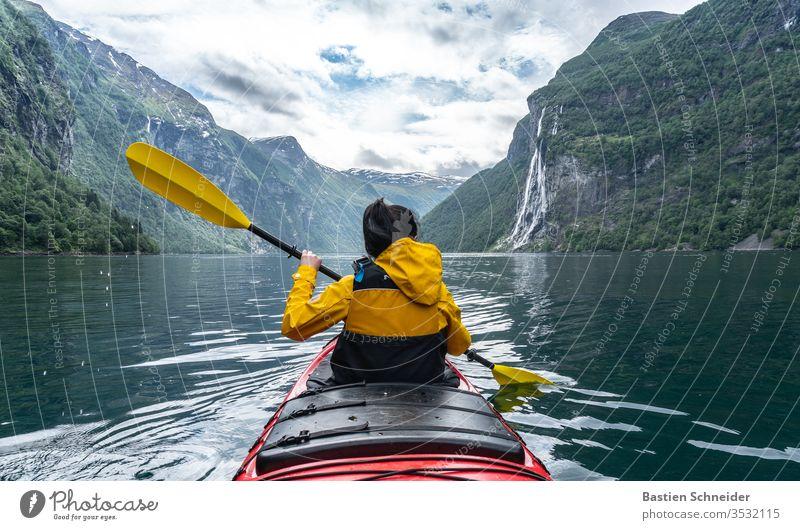 Frau paddelt im Geirangerfjord, Norwegen Berge u. Gebirge Landschaft Fjord Umwelt Farbfoto Wasserfall Schönes Wetter Sonnenlicht Wolken Außenaufnahme