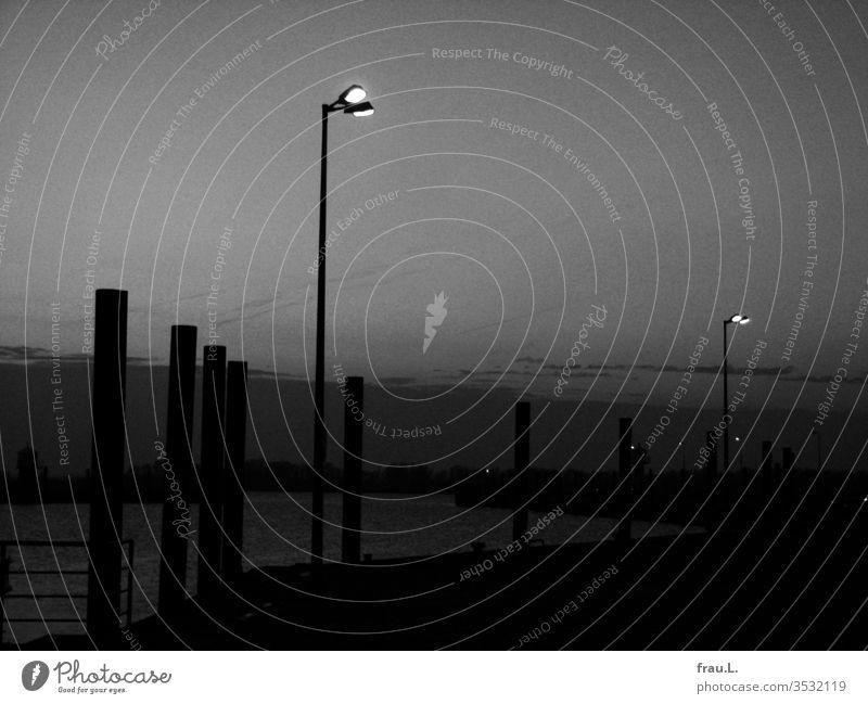 """""""Wenn sich die späten Nebel drehen, werd' ich an der Laterne stehen"""" im Hafen von Glückstadt. Abend Dämmerung Hafenstadt Laternen Elbe"""