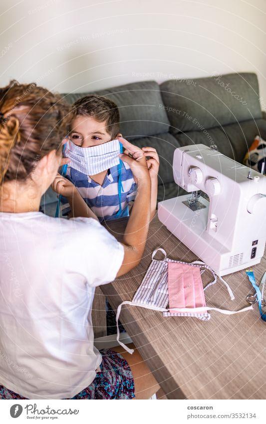 Mutter setzt ihrem Sohn eine selbstgemachte Gesichtsmaske auf Erwachsener Junge Business Kinder Kleidung Bekleidung Korona Coronavirus COVID kreativ Design