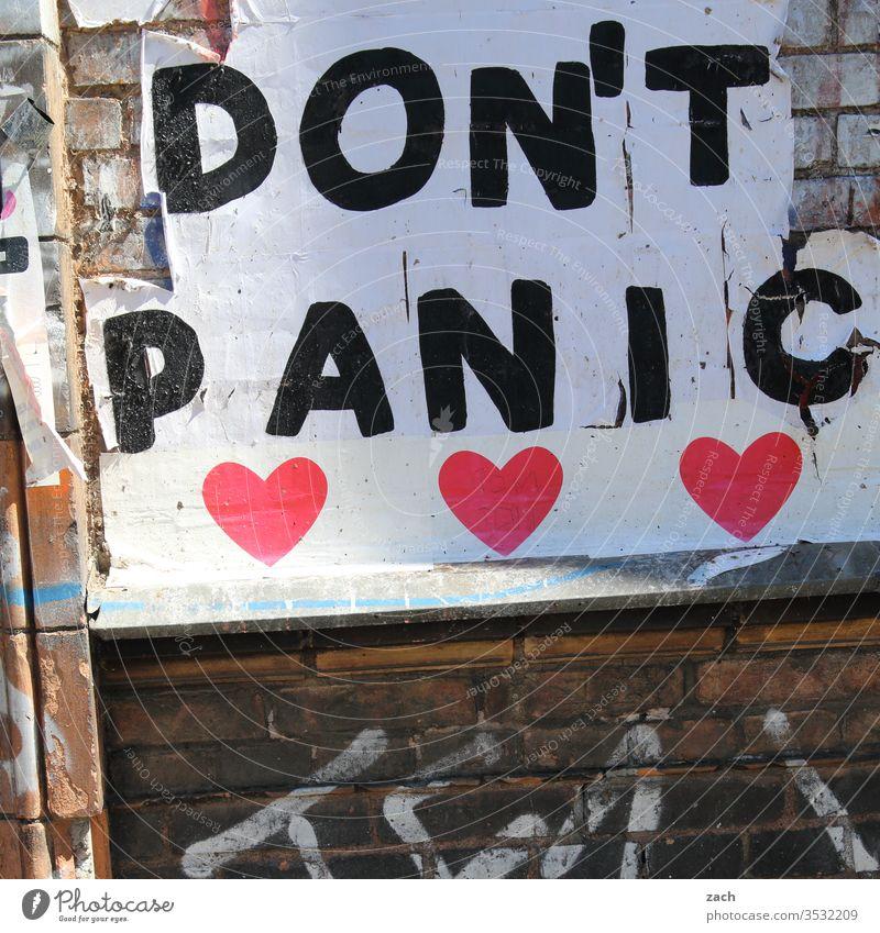 Fassade mit der Aufschrift Don't Panic Mauer Wand Stein Backstein Strukturen & Formen rot alt Graffiti Kunst Verfall Schablone kaputt Vergänglichkeit Papier