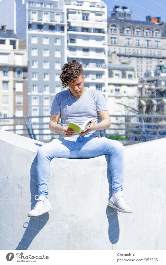 Mann mit moderner Frisur sitzt auf einer weißen Wand und liest ein Buch vertikal Großstadt urban Sitzen Park Straße sonnig Sonne Sonnenbad Sommer