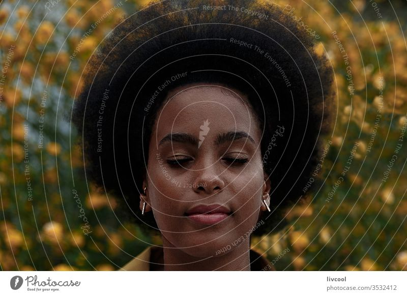 nachdenkliche Afro-Frau mit geschlossenen Augen in einem Garten schwarze Frau Mädchen Träumer Afrofrau geschlossene Augen jung Menschen Porträt Lifestyle cool