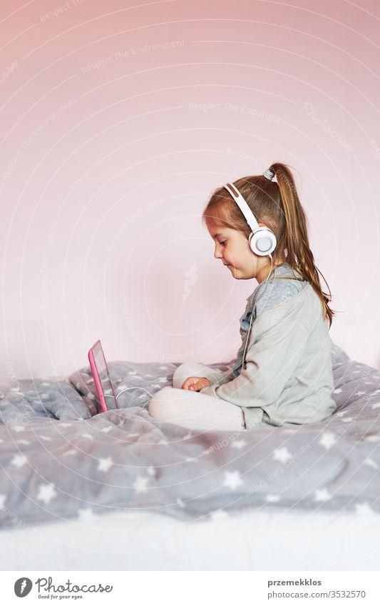 Kleines Mädchen im Vorschulalter lernt online Rätsel lösen und spielt zu Hause Lernspiele auf Tablet Kind zuschauend hören Lernen lehrreich Geduldsspiel Bett