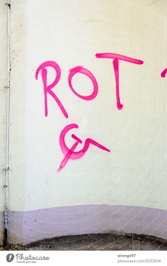 Hammer, Sichel und das Wort ROT mit roter Farbe auf eine beige Wand gesprayt Schrift Sprühfarbe sprühen Graffiti sprayen Schriftzeichen Menschenleer Tag