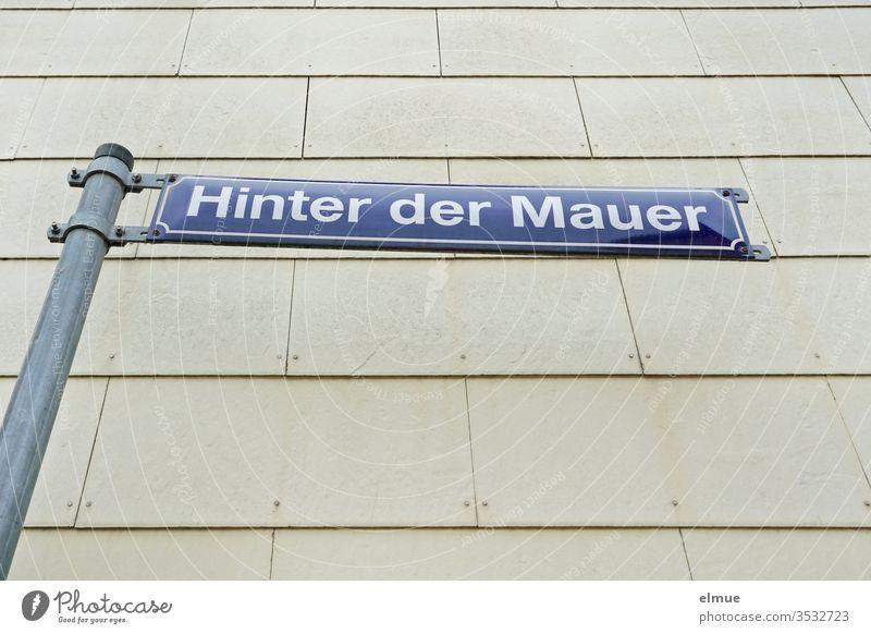 """blaues Straßenschild """"Hinter der Mauer"""" vor einer grauen Fassade Straßenname Hinweis Schild Beschilderung Wand Schilder & Markierungen Hinweisschild"""