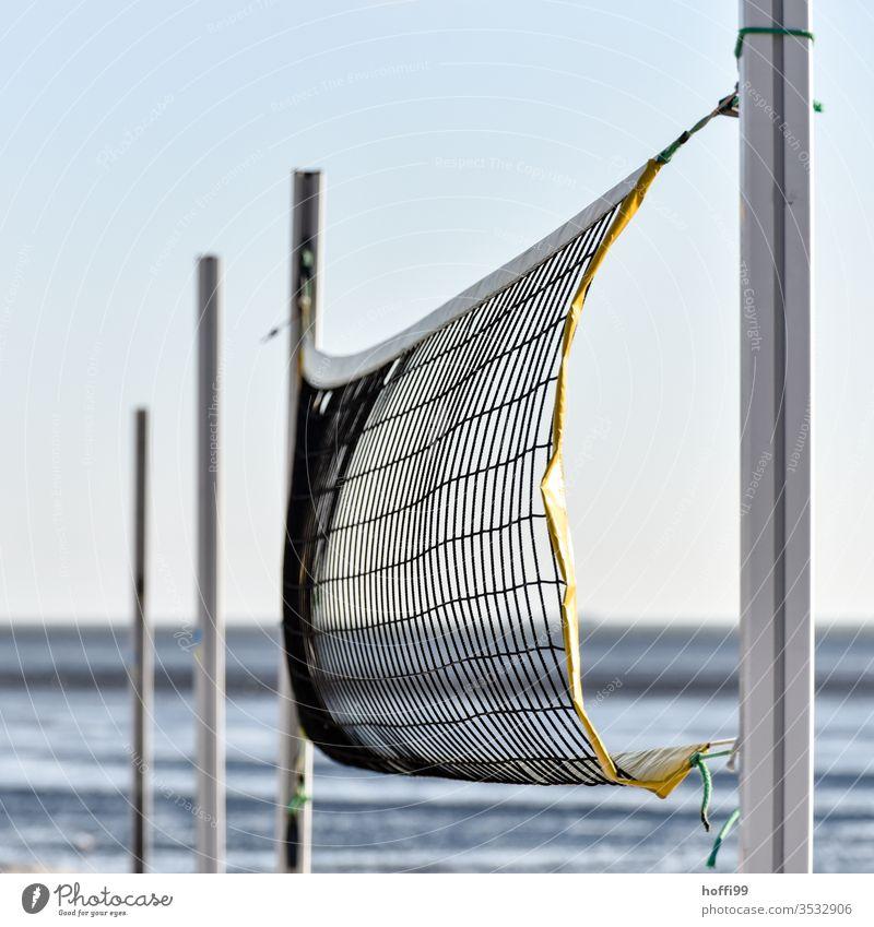 Der Wind spielt mit dem Volleyballnetzt am Strand - keiner da. Volleyballfeld Sport Beachvolleyball Sommer Sport Sand Netz Spielen Menschenleer Ballsport blau