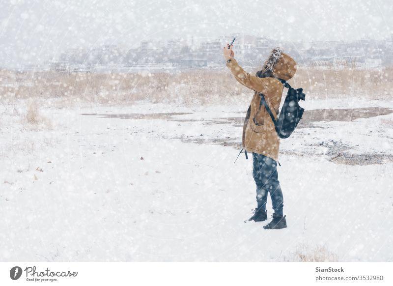 Frau fotografiert in verschneiter Landschaft Schnee Winter laufen Telefon Selfie nimmt Foto Smartphone mpbile kalt im Freien Schritt weiß Spaziergang Natur Mode