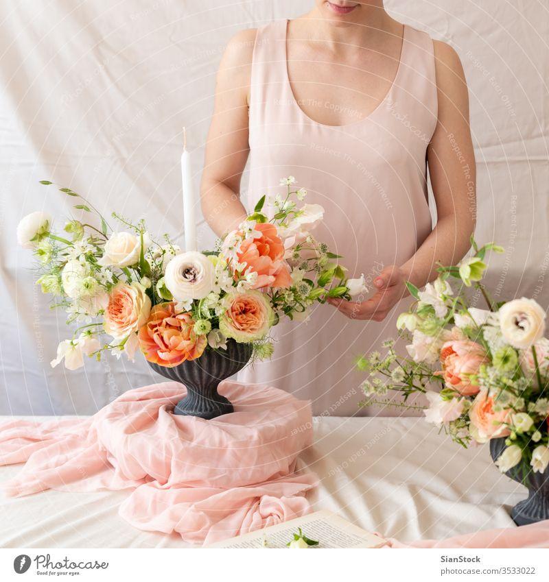 Frauenhände berühren einen Blumenstrauß. Tisch jung Kaukasier Halt Beteiligung Hände Hand Kleid weiß Vase Kerzen weich Licht Dekoration & Verzierung Hintergrund