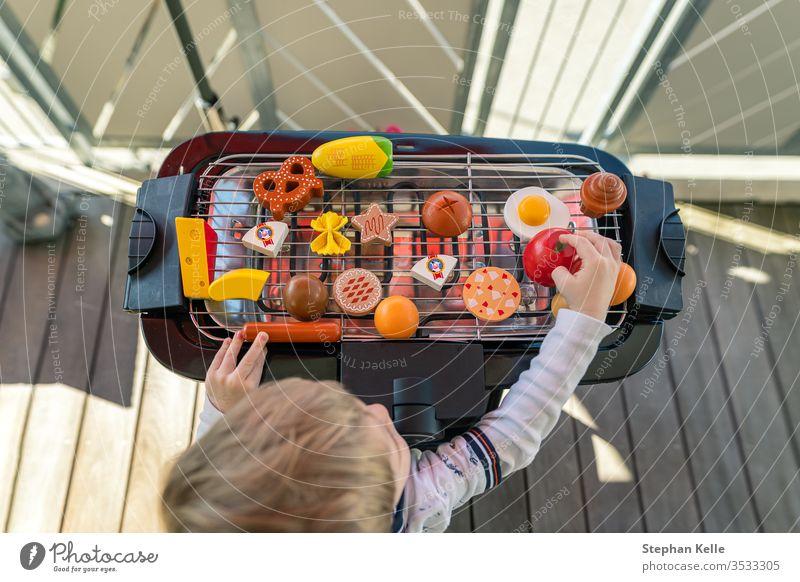 Ein kleiner Junge fängt an zu grillen, indem er auf dem Balkon mit seinem Gemüse und seinem Spielzeug für Wurstwaren spielt. Er kreiert ein leckeres Essen für seine Familie.