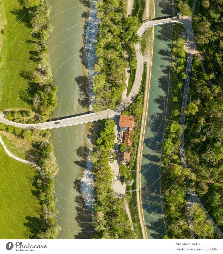 Draufsicht von einer Drohne auf ein fahrendes Auto an einer Brücke über einen Fluss mit einem Neffenwald und einem Haus Luftaufnahme Dröhnen PKW Natur Frühling