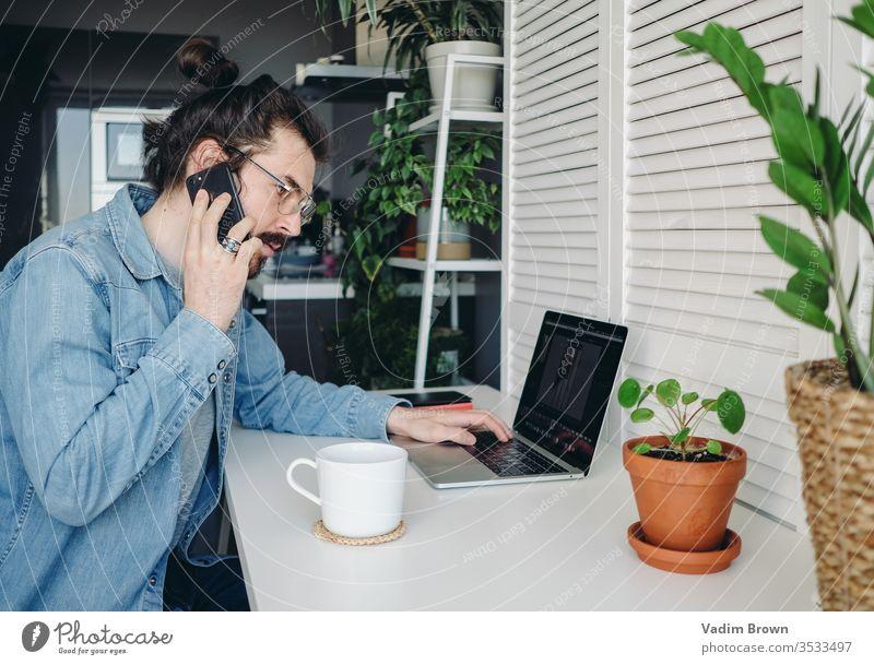 Junger Mann mit Bart sitzt auf dem Stuhl und benutzt einen Laptop. Freiberufliche Arbeit von zu Hause im Quarantänekonzept Video-Chat Online-Shopping