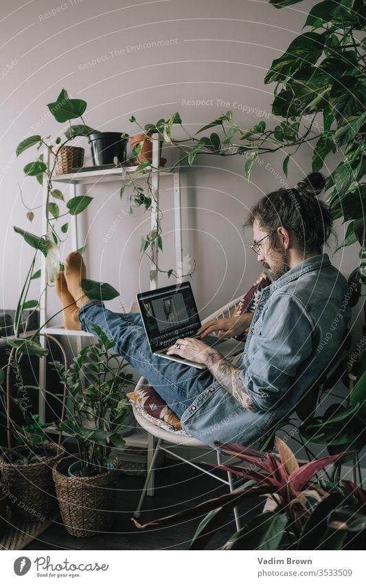 Junger Mann mit Bart sitzt auf dem Stuhl und benutzt einen Laptop. Freiberufliche Arbeit von zu Hause im Quarantänekonzept Appartement attraktiv Browsen
