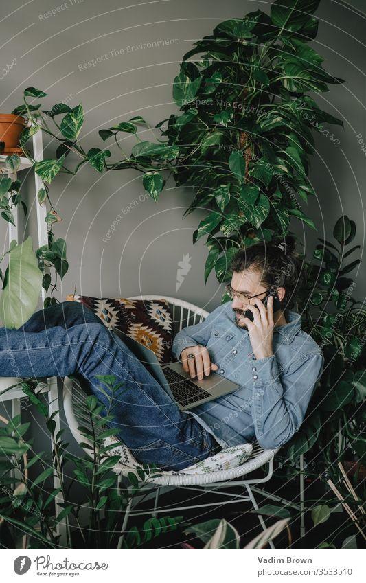 Junger Mann mit Bart sitzt am Tisch und benutzt Laptop heimwärts Telefon Arbeit Arbeit von zu Hause aus Verwendung des Laptops mit Hilfe von Technologie