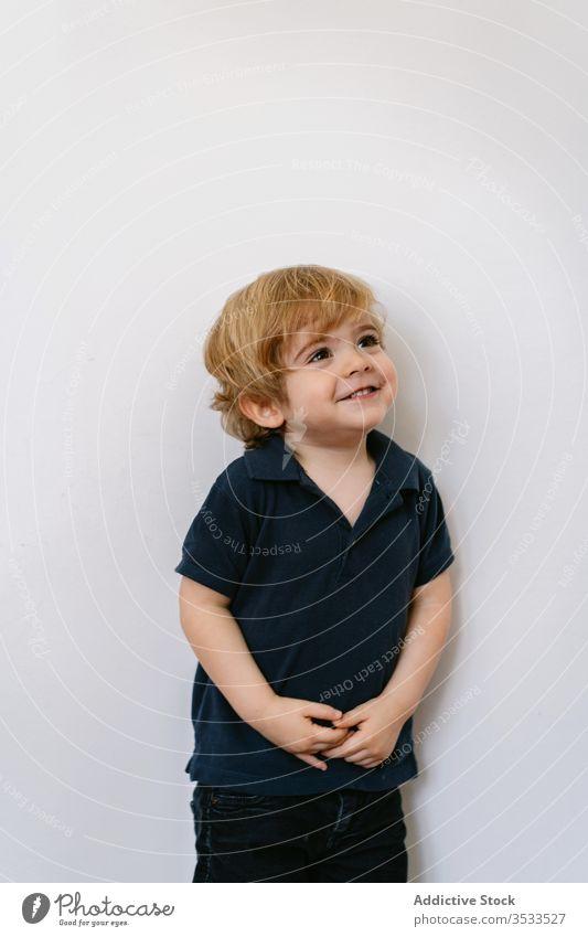 Glückliches kleines Kind steht in einer Weile in der Wand wenig Junge Energie Vorschule bezaubernd Freude Lachen Spaß Kindheit expressiv spielerisch Lächeln