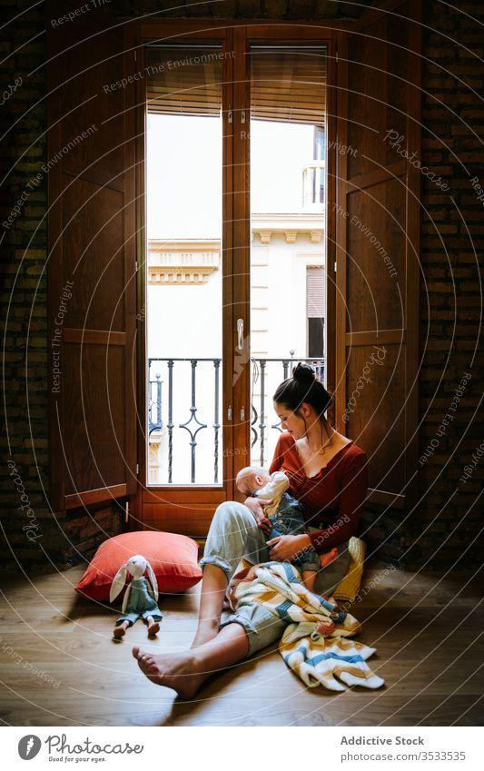 Glückliche Mutter stillt Baby am Fenster Stillen Futter Brust heimwärts Liebe ruhen gemütlich sitzen Frau niedlich Raum Umarmung Umarmen Lächeln Kind Kindheit