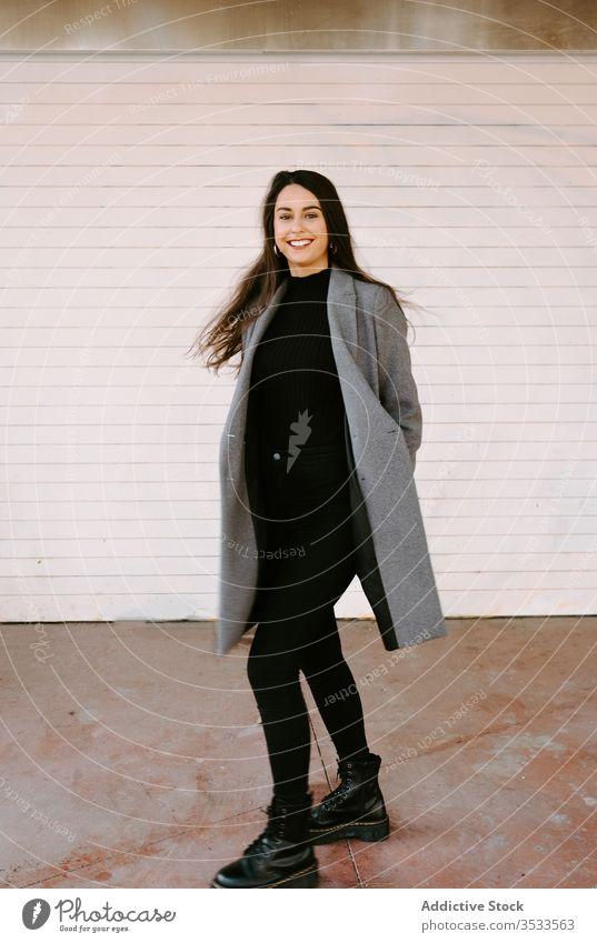 Glückliche junge Frau dreht sich auf der Straße spinnen Großstadt Lächeln urban Stil Spaß Tanzen aufgeregt Mantel trendy Gebäude Wand Mode erstaunt Model Dame