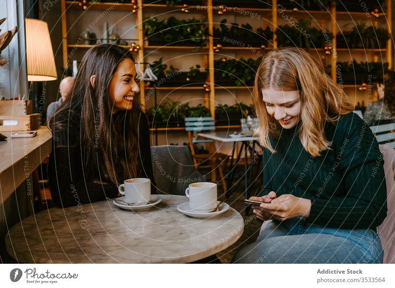 Freundinnen ruhen sich in gemütlichem Cafe aus Frauen Café Lachen Zusammensein Kaffee Smartphone benutzend Witz lässig Wochenende jung Sitzung Restaurant