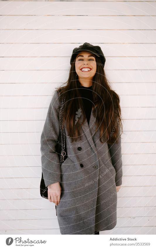 Selbstbewusste junge Frau an der weißen Wand Stil Straße selbstbewusst Verschlussdeckel Gebäude Mantel Outfit Model urban anhaben Accessoire Hut brünett