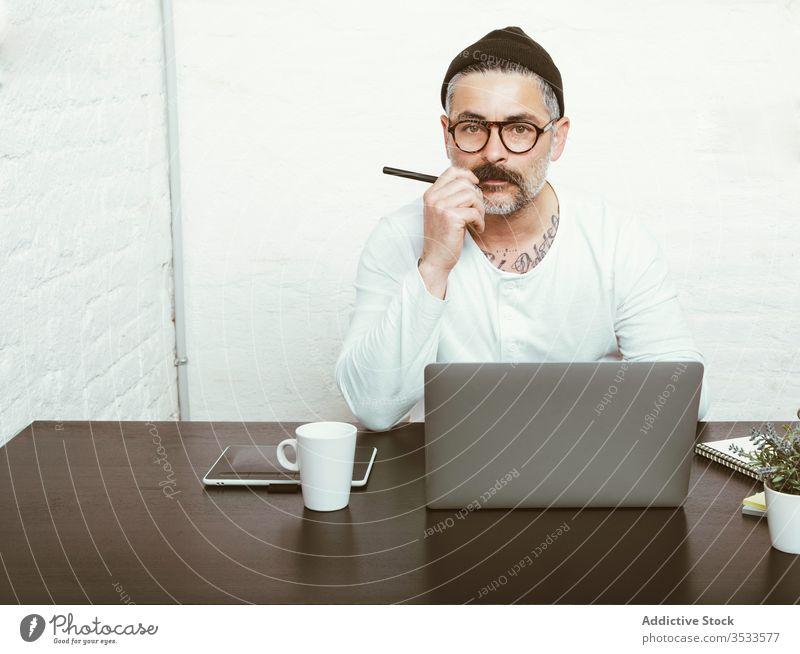 Erwachsener Mann arbeitet zu Hause am Laptop Arbeit freiberuflich benutzend Konzentration Quarantäne zur Kenntnis nehmen COVID19 Kopfbedeckung Brille männlich