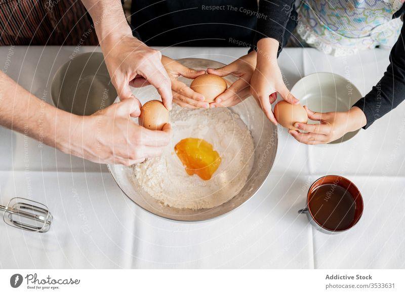 Pflanzeneltern und -kinder fügen bei der Backwarenzubereitung Zutaten hinzu Eltern Kinder Koch Gebäck Bestandteil hinzufügen Schalen & Schüsseln Ei Riss Küche