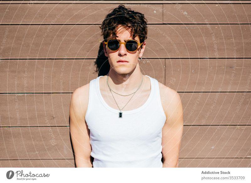 Stilvoller Mann an der Wand stehend Straße modern urban jung Großstadt Sonnenbrille Tanktop männlich trendy Model Hipster sonnig Gebäude Konstruktion cool