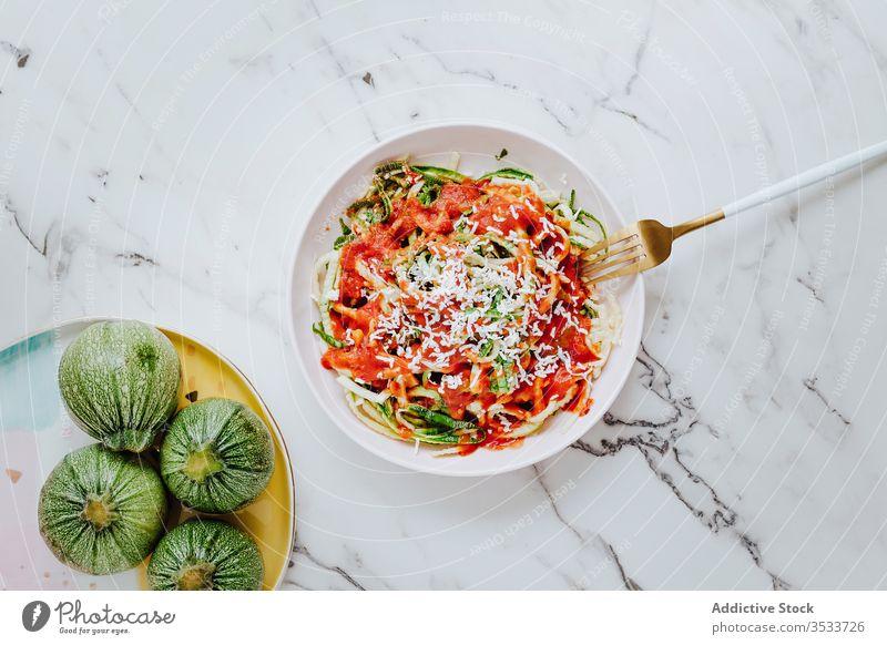Hausgemachte Zucchini-Nudeln mit Käse und Tomatensauce Spätzle Saucen gesunde Ernährung Veggie natürlich mischen grün kulinarisch Gabel Mahlzeit Teller rot