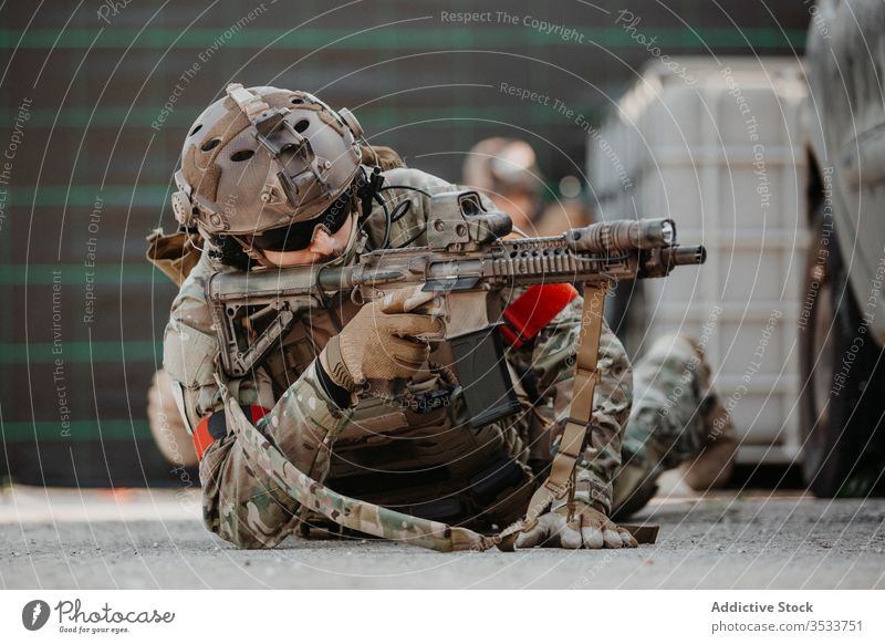 Soldat zielt mit Airsoft-Gewehr während des taktischen Spiels Mann schießen Pistole zielen Tarnung Boden Lügen männlich Uniform Militär Erwachsener behüten