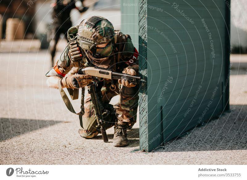kniender Airsoft-Spieler Flinte Tarnung Schießen Pistole Konflikt Waffe Krieg Ziel Sport Training op Militär positionieren männlich aktiv Schlacht sportlich