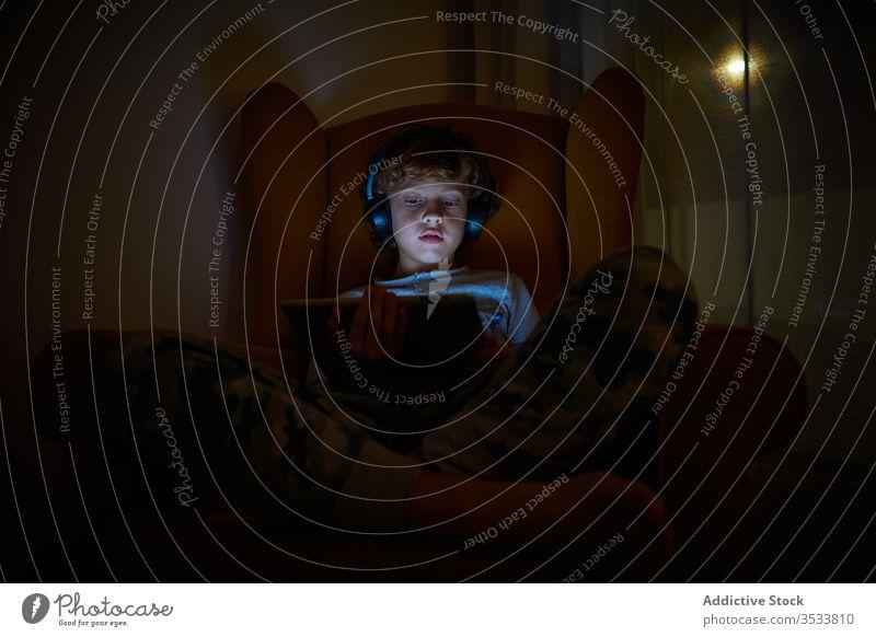 Kind, das nachts mit Kopfhörern auf einem Sessel in einer Zimmerecke sitzt und ein Tablett auf dem Schoss hat Junge Multimedia Mitteilung zuhören Spiel spielen