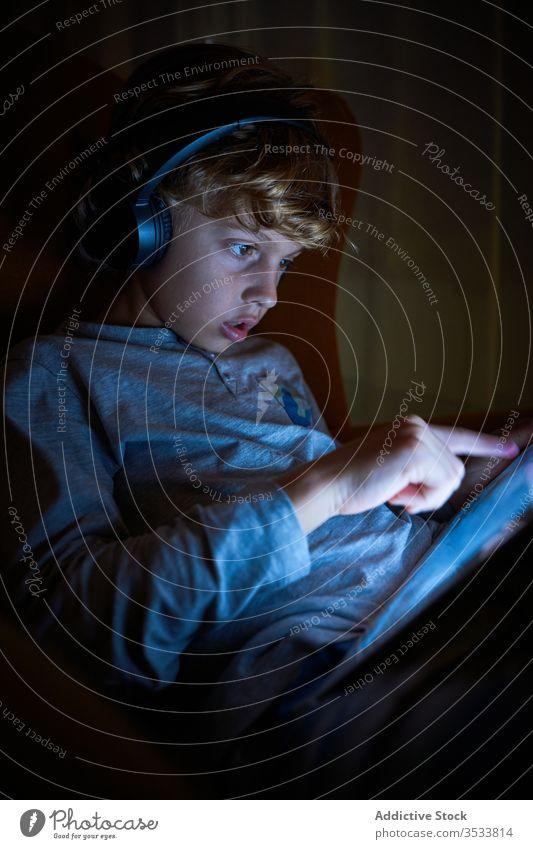 Vertikales Foto eines Kindes, das mit Kopfhörern auf einem Sofa sitzt und nachts den Bildschirm eines Tabletts berührt Junge Zeigen berührend interagieren