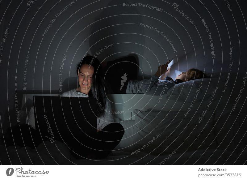Mutter und Sohn benutzen nachts Geräte Nacht Bett benutzend Süchtige dunkel heimwärts Schlafzimmer Frau Junge Browsen Apparatur Tablette Laptop Zusammensein