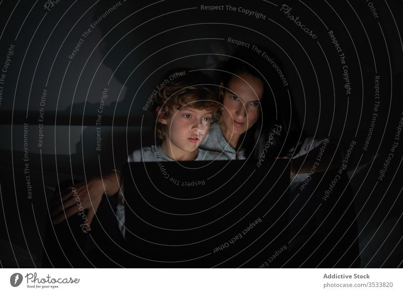 Fröhliche Mutter und Sohn mit Laptop im Bett heimwärts Nacht Zusammensein zuschauen Film Lächeln dunkel benutzend Schlafzimmer Frau Junge Kind Lügen Gerät