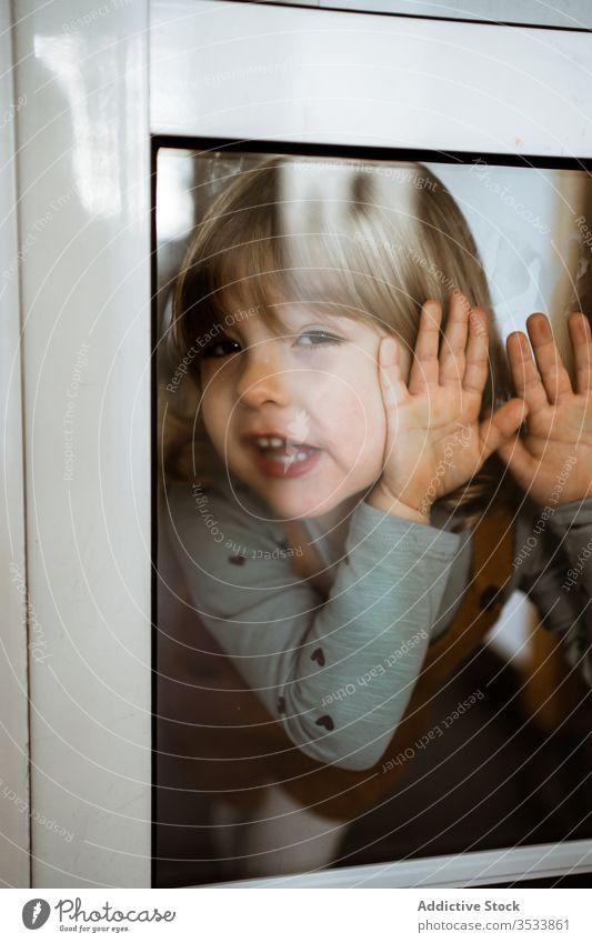 Glückliches kleines Mädchen hinter dem Fenster heimwärts Lächeln lässig niedlich wenig berühren Glas Kind heiter Kindheit Raum spielerisch neugierig ruhen