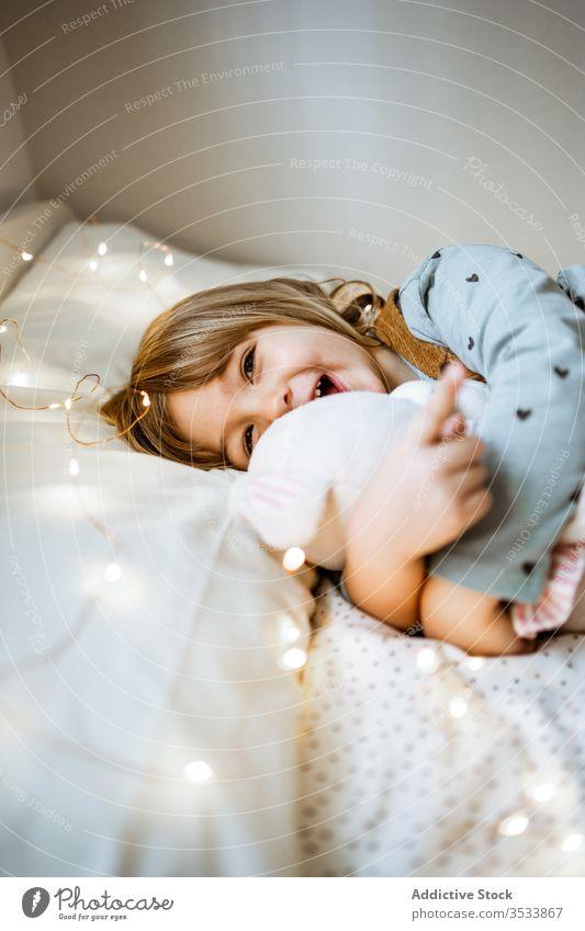 Glückliches Mädchen spielt auf weichem Bett spielen Spielzeug Umarmung Lachen Lichterkette Plüsch Lügen aufgeregt Kind Liebe Girlande Schlafzimmer wenig