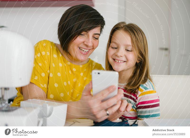 Fröhliche Näherin nimmt sich mit Tochter Mutter Selfie Smartphone Werkstatt Schneider Lächeln heimwärts Arbeit Zusammensein Frau Mädchen Tisch heiter