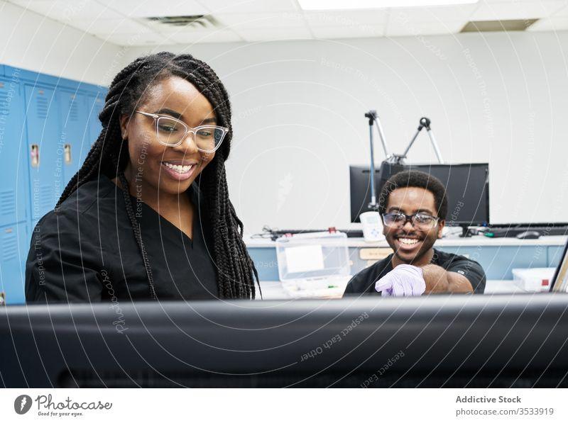 Ethnische Kollegen untersuchen Daten auf Laborcomputer diskutieren Computer ethnisch Zusammensein Arbeit klug modern Mann Frauen Uniform Zeitgenosse forschen