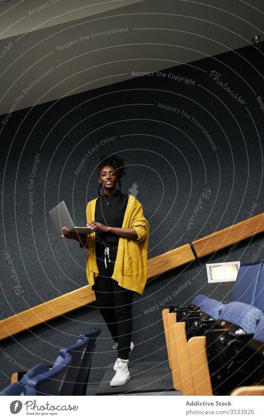 Schwarzer Student mit Laptop im Hörsaal Frau Schüler benutzend Aula ethnisch lernen modern Universität dozieren Saal Klassenraum Publikum lässig Browsen Bildung